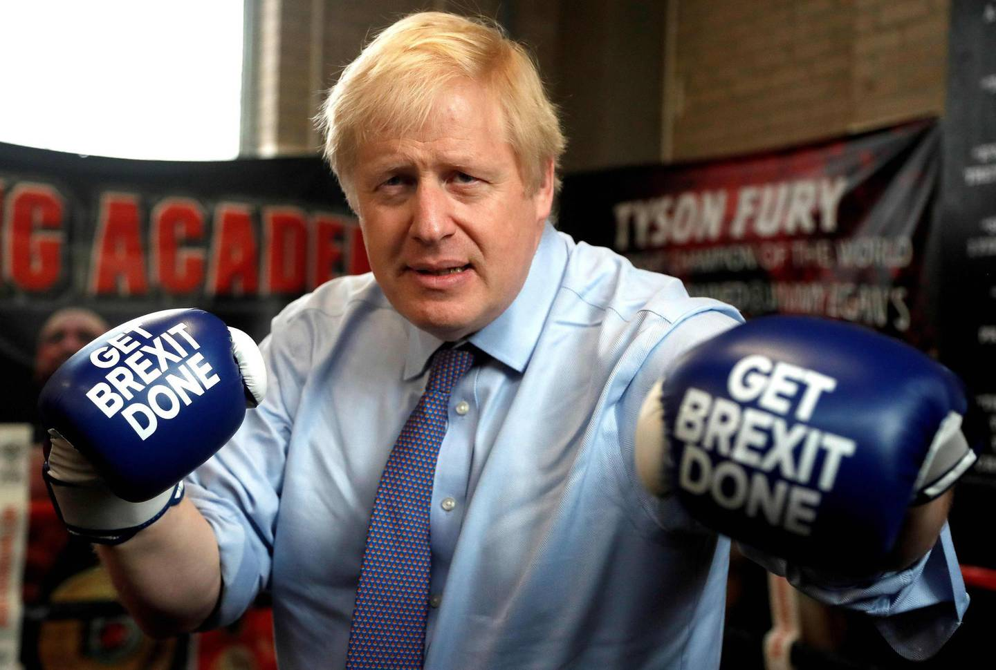 """(FILES) In this file photo taken on November 19, 2019 Britain's Prime Minister and leader of the Conservative Party, Boris Johnson wears boxing gloves emblazoned with """"Get Brexit Done"""" as he poses for a photograph at Jimmy Egan's Boxing Academy in Manchester north-west England on November 19, 2019. Electoral success, Brexit, a global health crisis that left him near death, divorce, engagement and even a new baby. Boris Johnson has had an eventful 12 months in anyone's book. Johnson, 56, marks his first anniversary as Britain's prime minister on Friday, having had what one lawmaker described to the Guardian newspaper as a """"hell of a year"""". But his toughest test could yet be to come, as the full impact of the coronavirus outbreak bites on the UK economy, which has been battered by three months of enforced shutdown. / AFP / POOL / Frank Augstein"""