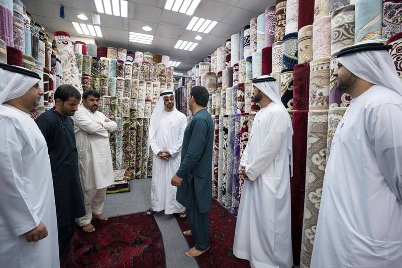 ABU DHABI, UNITED ARAB EMIRATES -  February 22, 2018: HH Sheikh Mohamed bin Zayed Al Nahyan, Crown Prince of Abu Dhabi and Deputy Supreme Commander of the UAE Armed Forces (C), speaks with staff at Al Safa Carpet shop, in the carpet market of the Mina Zayed Port. Seen with HE Jassem Mohamed Bu Ataba Al Zaabi, Chairman of Abu Dhabi Executive Office and Abu Dhabi Executive Council Member (L), HE Mohamed Mubarak Al Mazrouei, Undersecretary of the Crown Prince Court of Abu Dhabi (2nd R), and HH Sheikh Theyab bin Mohamed bin Zayed Al Nahyan, Chairman of the Department of Transport, and Abu Dhabi Executive Council Member (R).  ( Ryan Carter for the Crown Prince Court - Abu Dhabi ) ---