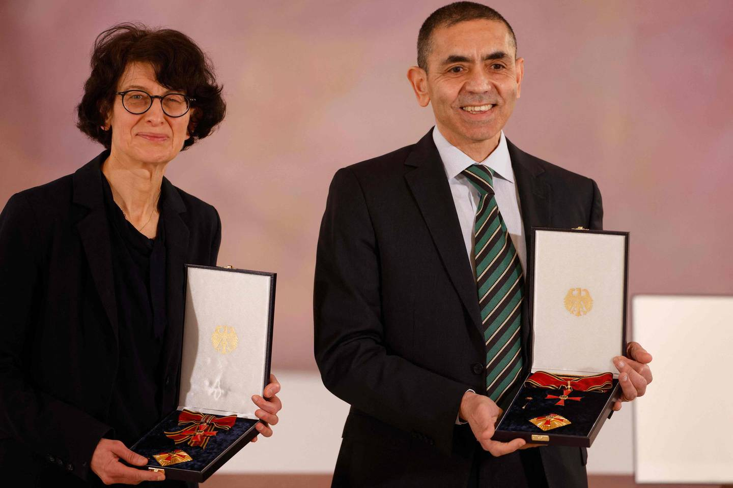 Ozlem Tureci (L) and her husband Ugur Sahin, both scientists and founders of BioNTech, pose with their orders after they were awarded the Federal Cross of Merit (Bundesverdienstkreuz) by the German President on March 19, 2021 at the presidential Bellevue Palace in Berlin. / AFP / POOL / Odd ANDERSEN