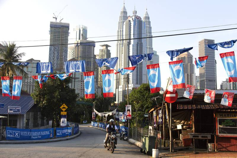 A motorcyclists rides past campaign flags and banners as the Petronas Twin Towers stand in the background in Kuala Lumpur, Malaysia, on Tuesday, May 8, 2018. Malaysia is holding a general election on May 9. Photographer: Ore Huiying/Bloomberg