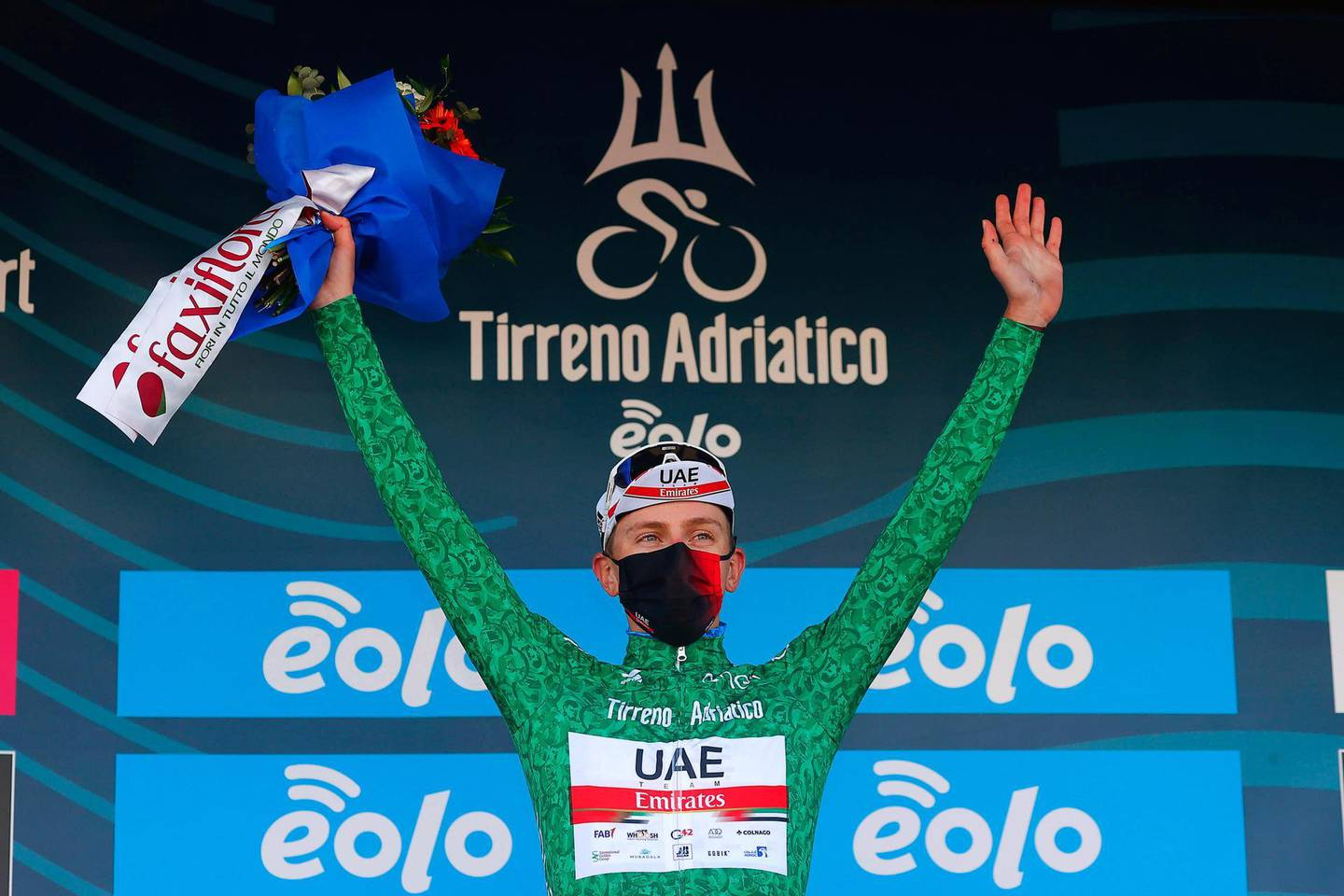epa09076789 Slovenian rider Tadej Pogacar of the UAE-Team Emirates team celebrates on the podium after retaining the best climber's green jersey following the 6th stage of the Tirreno-Adriatico cycling race over 169km from Castelraimondo to Lido di Fermo, Italy, 15 March 2021.  EPA/LUCA BETTINI