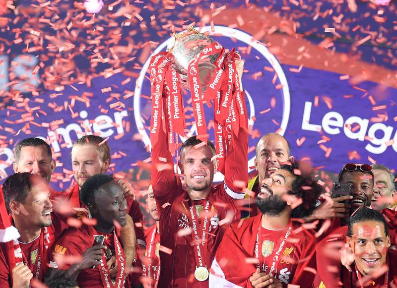 LIVERPOOL, ENGLAND - JULY 22: Jordan Henderson of Liverpool holds the Premier League Trophy aloft along side Mohamed Salah as they celebrate winning the League during the presentation ceremony of  the Premier League match between Liverpool FC and Chelsea FC at Anfield on July 22, 2020 in Liverpool, England. Football Stadiums around Europe remain empty due to the Coronavirus Pandemic as Government social distancing laws prohibit fans inside venues resulting in games being played behind closed doors. (Photo by Laurence Griffiths/Getty Images)