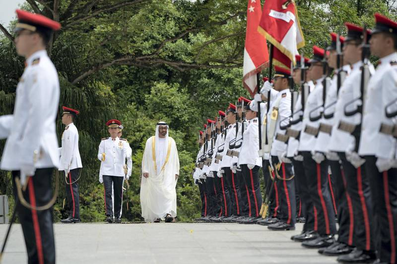 SINGAPORE, SINGAPORE - February 28, 2019: HH Sheikh Mohamed bin Zayed Al Nahyan, Crown Prince of Abu Dhabi and Deputy Supreme Commander of the UAE Armed Forces (C), inspects the honour guard during a reception hosted by HE Halimah Yacob, President of Singapore, (not shown), during a reception at the Istana presidential palace. ( Ryan Carter / Ministry of Presidential Affairs )