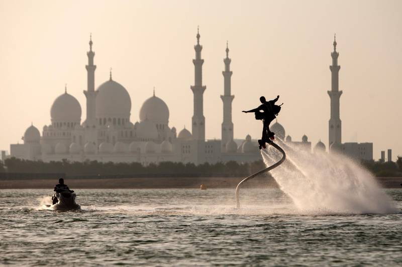 Abu Dhabi, United Arab Emirates, September 1, 2014:     A man flyboards in the Al Maqta Channel in front of the Sheikh Zayed Grand Mosque in Abu Dhabi on September 1, 2014. A Flyboard is a type of water jet-pack attached to a personal water craft which supplies propulsion to drive the device through air and water. Christopher Pike / The NationalReporter:  N/ASection: NewsPossible focal point
