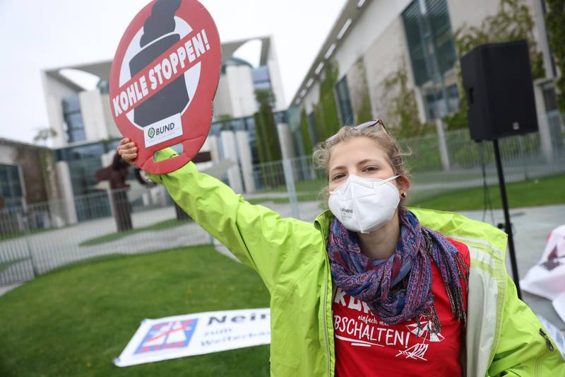 """BERLIN, GERMANY - MAY 12: A supporter of the Fridays for Future climate movement holds a sign that reads: """"Stop Coal!"""" outside the Chancellery where earlier in the day the government cabinet met to agree on amendments to Germany's climate protection law on May 12, 2021 in Berlin, Germany. Germany's Federal Constitutional Court recently ruled that the current law is insufficient in protecting future generations from the consequences of climate change, giving climate activists, including the nine young plaintiffs who brought the suit, a big victory. However many activists are saying the new government commitment of climate neutrality by 2045 is not enough and are demanding the same goal but for 2035. (Photo by Sean Gallup/Getty Images)"""