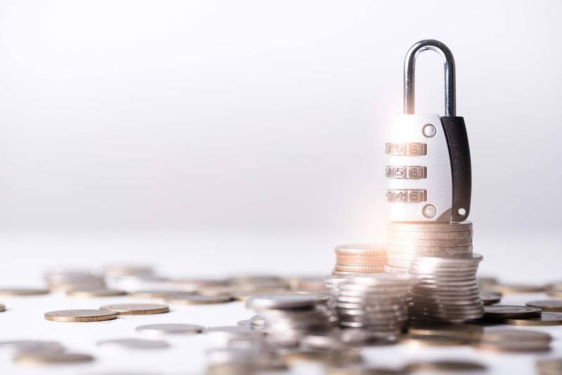 the abstract image of the coin stack which has the padlock on top and white copy space. the concept of saving, business, financial, cyber security and digital crime. Getty Images
