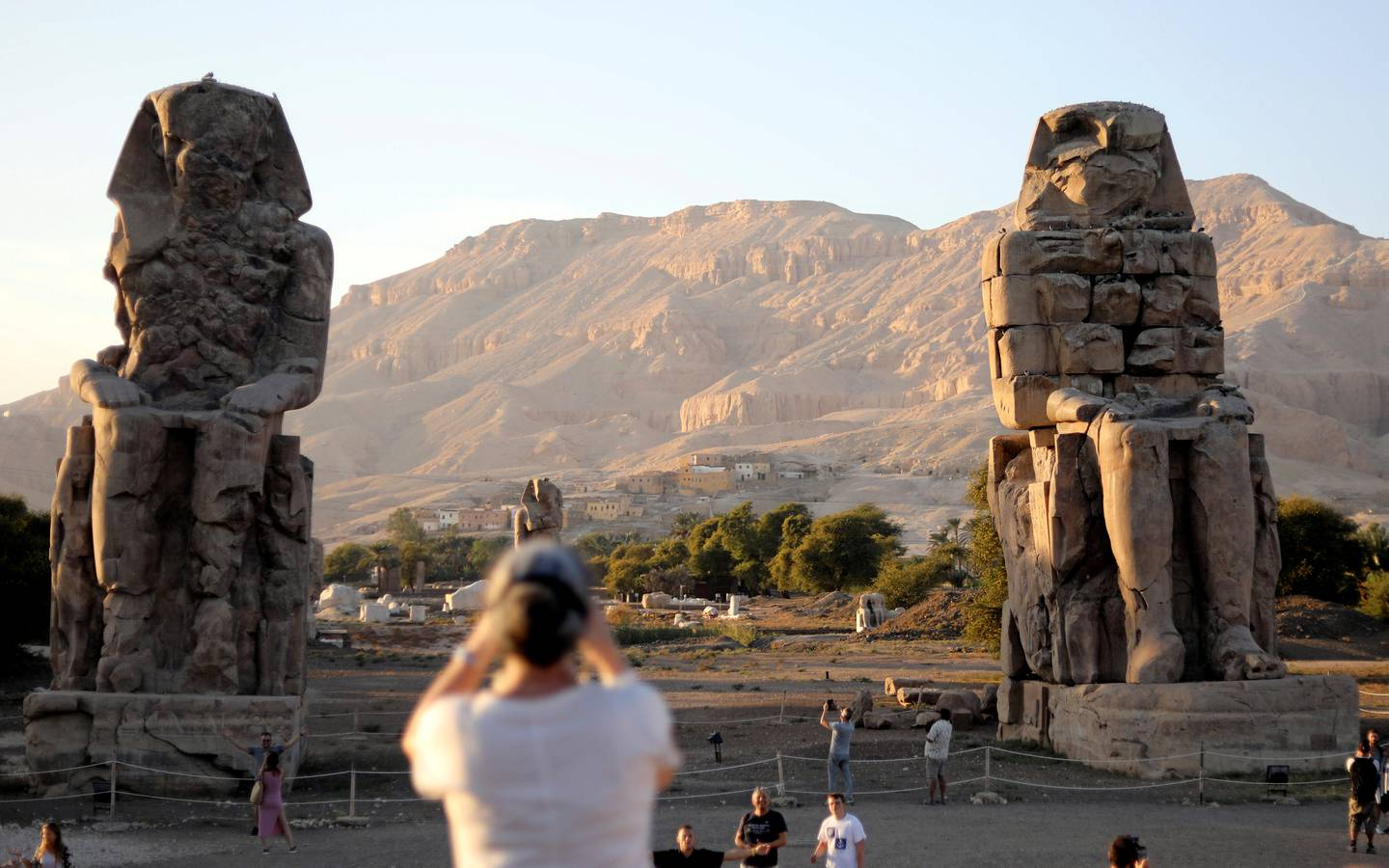 Tourists visit the Colossi of Memnon, the ruins of two stone statues that guarded the mortuary temple built for Pharaoh Amenhotep III, in Luxor, Egypt November 25, 2018. REUTERS/Mohamed Abd El Ghany