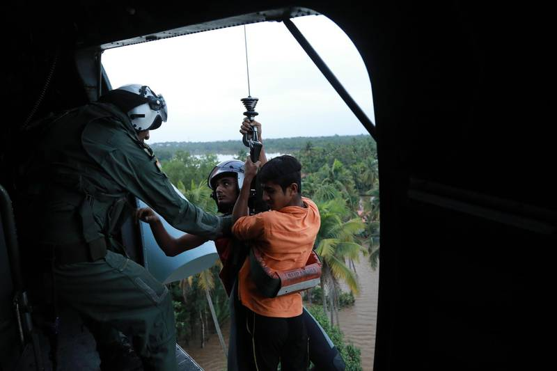Indian People are airlifted by Navy personnel during a rescue operation at a flooded area in Paravoor near Kochi, in the Indian state of Kerala on August 18, 2018. - Rescuers in helicopters and boats fought through renewed torrential rain on August 18 to reach stranded villages in India's Kerala state as the toll from the worst monsoon floods in a century rose above 320 dead. (Photo by - / AFP)