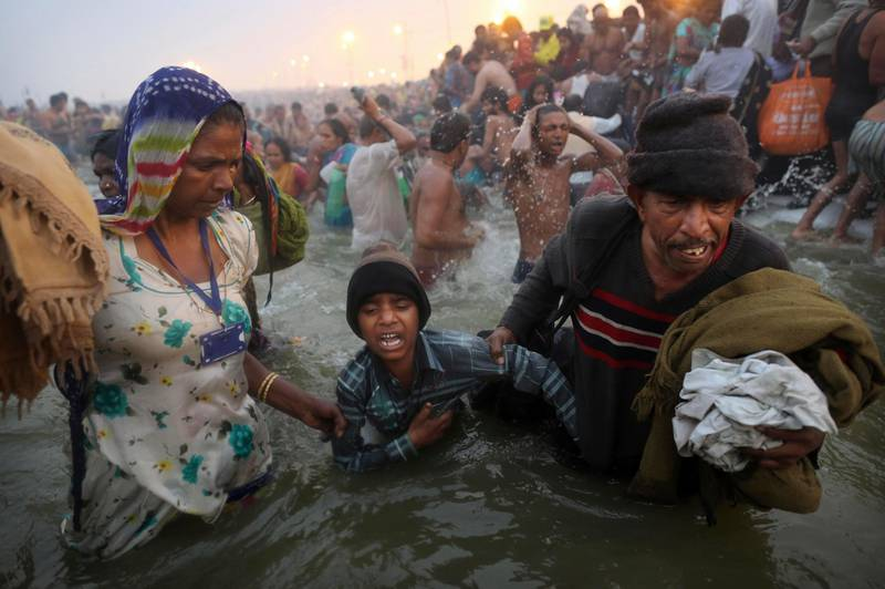 An Indian Hindu boy is reluctantly guided by his parents as they go for a dip fully clothed at Sangam, the confluence of the rivers Ganges, Yamuna and mythical Saraswati, during the royal bath on Makar Sankranti at the start of the Maha Kumbh Mela in Allahabad, India, early Monday, Jan. 14, 2013. Millions of Hindu pilgrims are expected to take part in the large religious congregation that lasts more than 50 days on the banks of Sangam during the Maha Kumbh Mela in January 2013, which falls every 12th year. (AP Photo/Kevin Frayer) *** Local Caption ***  India Maha Kumbh Mela.JPEG-0c588.jpg