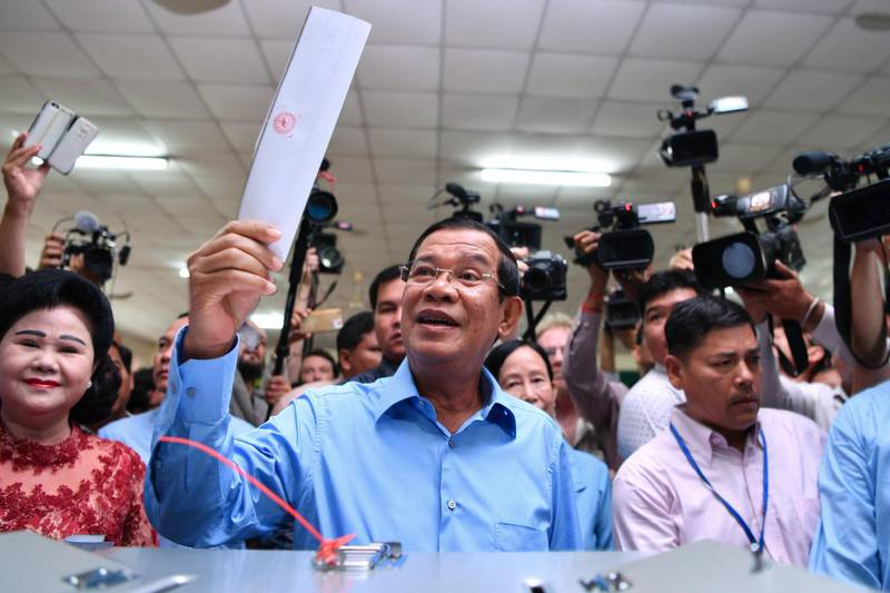 TOPSHOT - Cambodia's Prime Minister Hun Sen (C) prepares to cast his vote during the general election as his wife Bun Rany (L) looks on in Phnom Penh on July 29, 2018.  Cambodia went to the polls early on July 29 in an election set to be easily won by strongman premier Hun Sen after the only credible opposition was dissolved last year, effectively turning the country into a one-party state.  / AFP / Manan VATSYAYANA