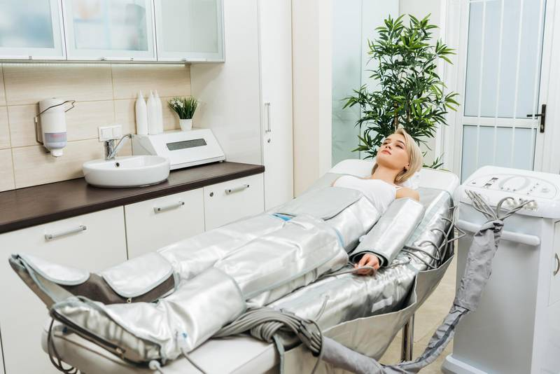 T322C8 Blonde girl lying on beauty couch during pressotherapy session in clinic. Alamy