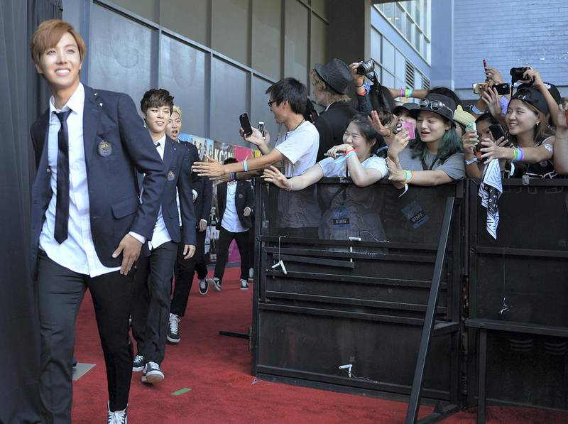 Members of Korean K-pop group BTS arrive on the red carpet during the K-CON 2014 (Korean Culture Convention) at the Los Angeles Memorial Sports Arena on August 10, 2014.  Having taken Asia by storm over the past decade with bubblegum looks and dance moves infused with military precision, South Korea's K-pop phenomenon continues to defy cultural barriers and find fans around the world. More Korean bands have multilingual members who can sing verses, carry choruses, and conduct interviews in English, Chinese, and Japanese so language is no longer a barrier.            AFP PHOTO/Mark RALSTON (Photo by MARK RALSTON / AFP)