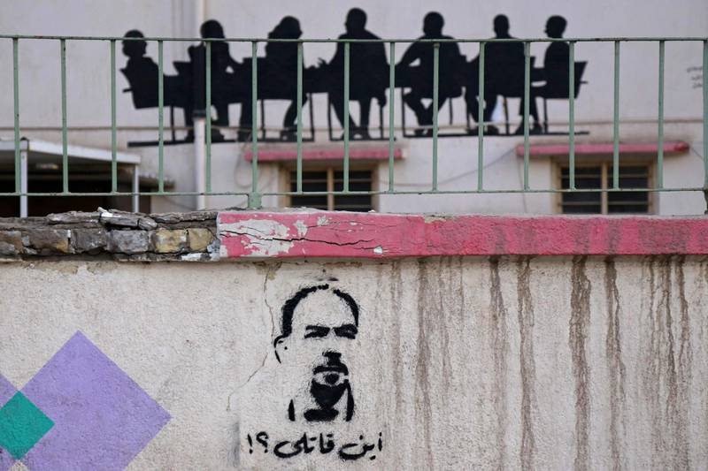 """A picture taken  on May 23, 2021 shows a graffiti reading in Arabic """"Where's my killer?"""" and depicting renowned Iraqi anti-government activist Ihab al-Wazni (Ehab al-Ouazni), who was shot dead in an ambush earlier this month,  in the shrine city of Karbala. A wave of deadly attacks on pro-democracy activists and journalists in Iraq have sparked mounting calls to boycott October parliamentary elections, as perpetrators go unpunished. Killings, attempted murder and abductions have targeted more than 70 activists since a protest movement erupted against government corruption and incompetence in 2019. / AFP / Mohammed SAWAF"""