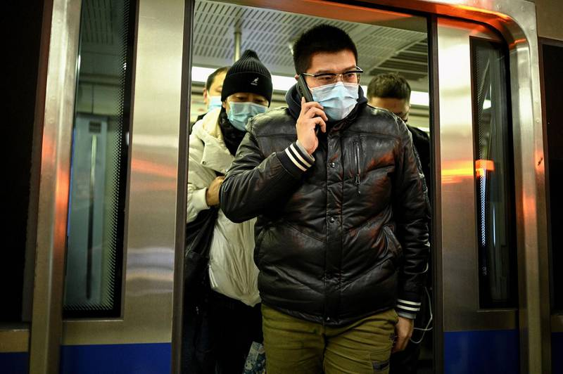 A man wearing a face mask uses his mobile phone as he exits a subway train in Beijing on December 17, 2020. / AFP / NOEL CELIS