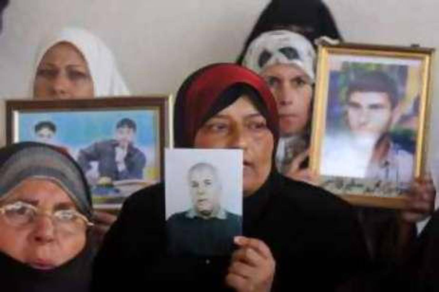 Palestinian women hold pictures of prisoners currently held in an Israeli jail during a protest calling for their release, outside the International Red Cross building in Gaza City, Monday, Aug. 18, 2008. Israel's Cabinet on Sunday approved the release of some 200 Palestinian prisoners as a goodwill gesture to the Palestinian government of moderate President Mahmoud Abbas. (AP Photo/Hatem Moussa)  *** Local Caption ***  JRL103_MIDEAST_ISRAEL_PALESTINIANS.jpg