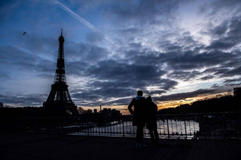 A couple look at the Eiffel Tower from the Debilly footbridge over the river Seine, at sunset on January 17, 2021, in Paris. / AFP / Martin BUREAU