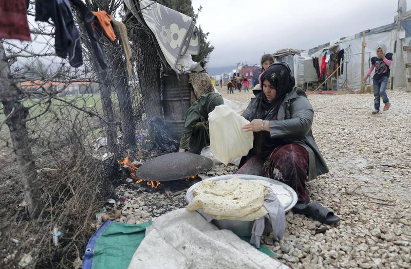 A Syrian woman prepares traditional bread for baking as she sits outside at a refugee camp on the outskirts of the town of Zahle in Lebanon's Bekaa Valley on January 26, 2018. Lebanon, a country of four million, hosts just under a million Syrians who have sought refuge from the war raging in their neighbouring homeland since 2011, many of whom live in informal tented settlements in the country's east and struggle to stay warm in the winter. / AFP PHOTO / JOSEPH EID