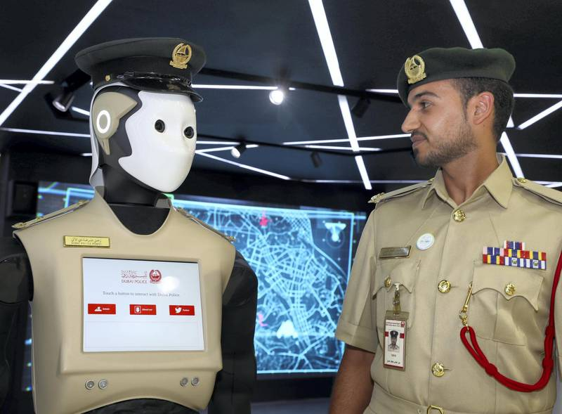 Dubai, United Arab Emirates - October 9th, 2017: Standalone. Bader Abbas Jaafar Hassan with the police robot at Dubai police stand at 37th GITEX technology week. Monday, October 9th, 2017 at World Trade Centre, Dubai.
