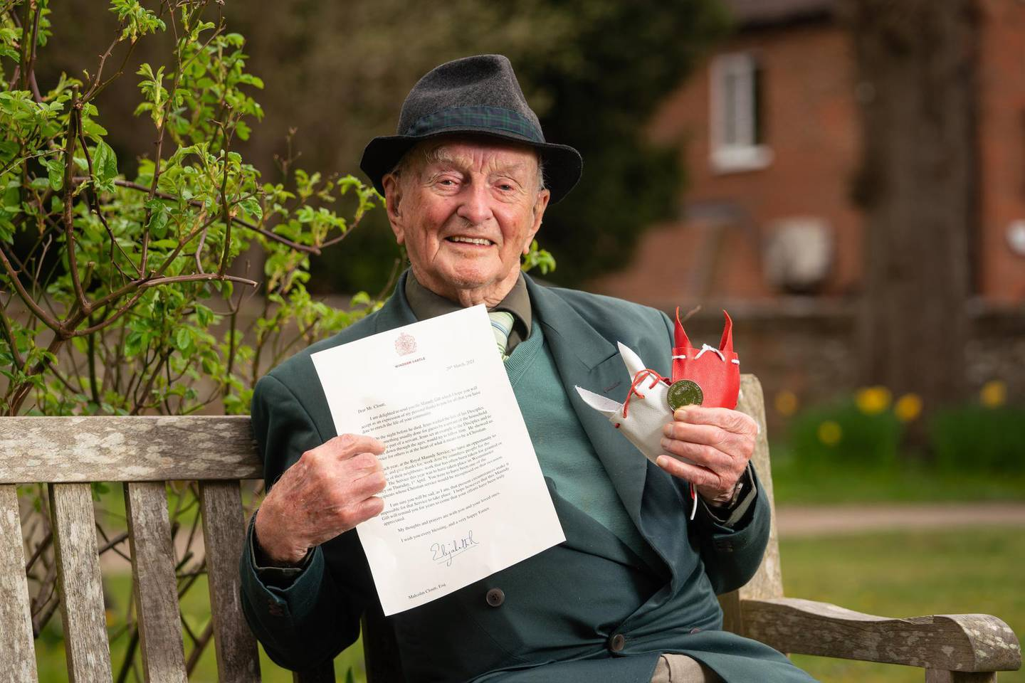 PRINCES RISBOROUGH, UNITED KINGDOM - MARCH 31: In this handout photo provided by Buckingham Palace, Malcolm Cloutt from Princes Risborough, Buckinghamshire, a veteran Second World War RAF pilot who served in Europe and Burma and turned 100 last year, and who is among this years recipients of Maundy money,  poses for a photo on March 31, 202 in Princes Risborough, United Kingdom. This year there are 190 Royal Maundy recipients who have been recognised by their dioceses for their outstanding contributions to their local church and community life. Queen Elizabeth II has written to those she would have presented with symbolic coins during the annual Royal Maundy service, but who instead have received the gift by post after the event was cancelled for the second year running due to coronavirus restrictions. (Photo by Dominic Lipinski -Buckingham Palace via Getty Images)