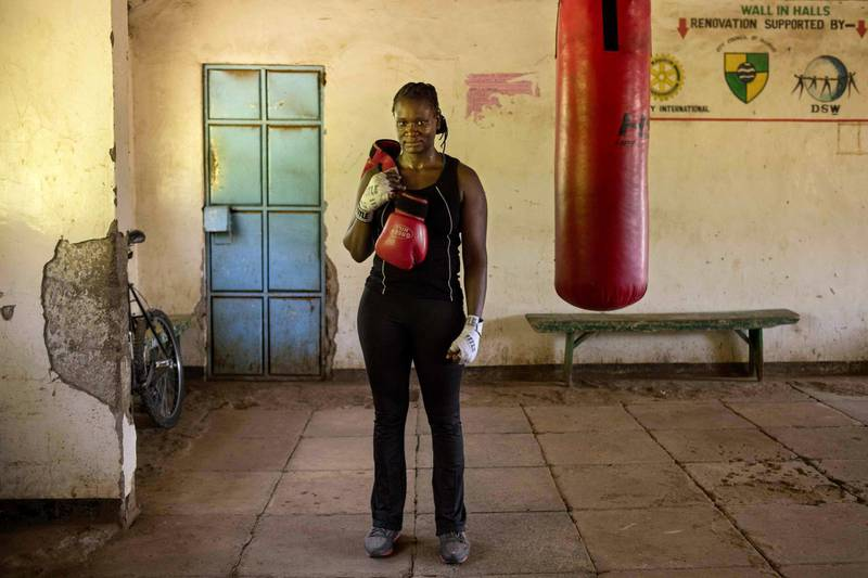 """To mark the occasion of International Women's Day on March 8, 2018 AFP presents a series of 45 photos depicting women performing roles or working in professions more traditionally held by men.  More images can be found in www.afpforum.com  Search SLUG  """"WOMEN-DAY -PACKAGE"""".  Sarah Achieng a 31 year-old professional boxer and sports administrator poses after her training session at Kariobangi social hall gym in Nairobi on February 27, 2018.  In the ring, battling flames or lifting off into space, women have entered professions generally considered as men's jobs. For International Women's Day, AFP met with women breaking down the barriers of gender-bias in the work world. / AFP PHOTO / Patricia ESTEVE"""