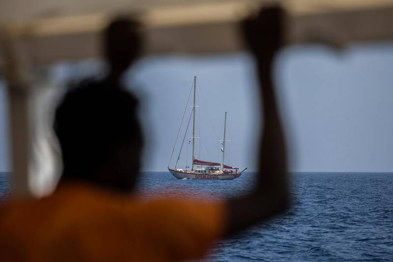 A migrant standing on the deck of the NGO Proactiva Open Arms boat looks at the Open Arms Astral sailboat on July 2, 2018. A Spanish NGO said on June 30, 2018 it had rescued 59 migrants as they tried to cross the Mediterranean from Libya and would dock in Barcelona in Spain after Italy and Malta refused access. The news comes two days after three babies were found dead and 100 more went missing in a shipwreck off Libya that Proactiva Open Arms, whose charity rescue boat was in the area, said could potentially have been avoided.  -   / AFP / Olmo Calvo