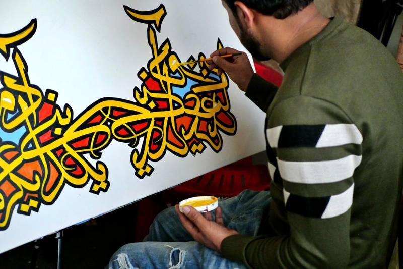 Pictured: A male artist paints a canvas at the ArtLords headquarters in Kabul. Photo by Charlie Faulkner February 2021