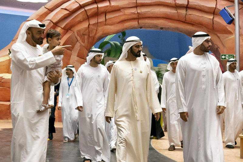 YAS ISLAND, ABU DHABI, UNITED ARAB EMIRATES - July 23, 2018: HH Sheikh Mohamed bin Zayed Al Nahyan, Crown Prince of Abu Dhabi and Deputy Supreme Commander of the UAE Armed Forces  (L), HH Sheikha Salama bint Diab bin Mohamed bin Zayed Al Nahyan (2nd L), HH Sheikh Mohamed bin Rashid Al Maktoum, Vice-President, Prime Minister of the UAE, Ruler of Dubai and Minister of Defence (C) and HE Mohamed Khalifa Al Mubarak, Chairman of the Department of Culture and Tourism and Abu Dhabi Executive Council Member (R) attend the opening of Warner Bros. World Abu Dhabi. Seen with HH Sheikh Hamdan bin Mohamed Al Maktoum, Crown Prince of Dubai (back).   ( Hamad Al Kaabi / Crown Prince Court - Abu Dhabi ) ---