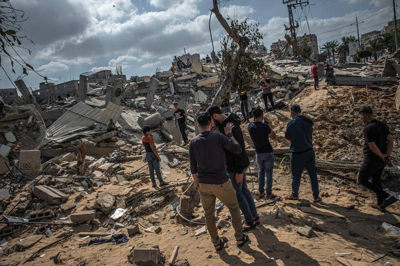 GAZA CITY, GAZA - May 13: Men walk on the rubble of a residential building in Gaza City, Gaza Strip, that was destroyed by an Israeli airstrike, on May 13, 2021 in Gaza City, Gaza. More than 65 people in Gaza and seven people in Israel have been killed in continued cross-boarder rocket exchanges as violence continues to escalate bringing fears of war. The escalation which erupted on Monday comes after weeks of rising Israeli-Palestinian tension in East Jerusalem, which peaked with violent clashes inside the holy site of Al-Aqsa Mosque. (Photo by Fatima Shbair/Getty Images)