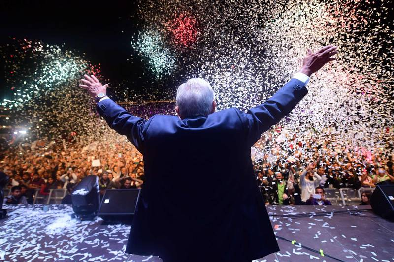 """TOPSHOT - Newly elected Mexico's President Andres Manuel Lopez Obrador (C), running for """"Juntos haremos historia"""" party, cheers his supporters at the Zocalo Square after winning general elections, in Mexico City, on July 1, 2018.  / AFP / PEDRO PARDO"""
