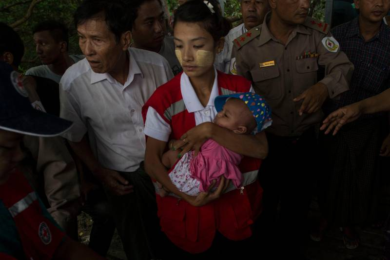 TOPSHOT - A member of Myanmar's Red Cross carries a baby as he arrives in Sittwe jetty, in Rakhine State on August 30, 2017. At least 18,500 Rohingya have fled into Bangladesh in the last six days since renewed fighting broke out between militants and the army in neighbouring Myanmar, the International Organization for Migration said. / AFP PHOTO / STRINGER