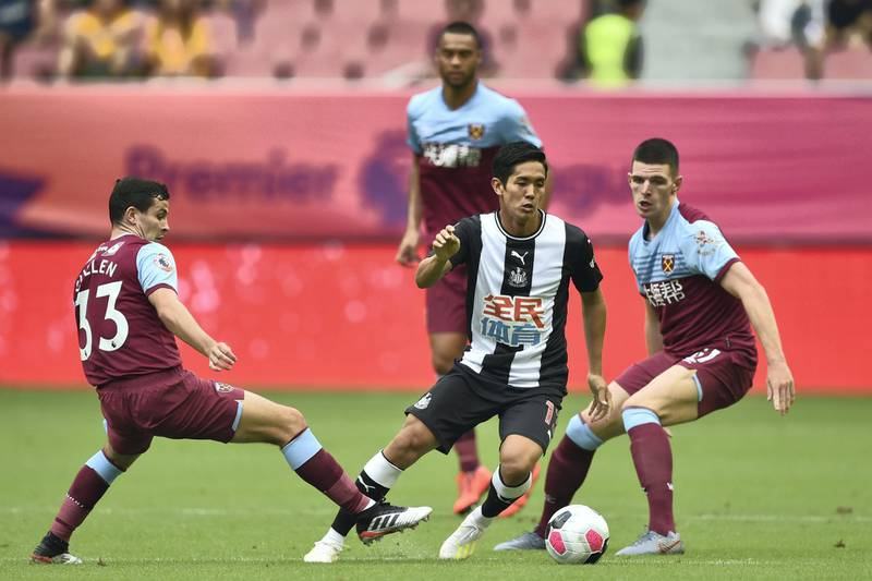 Newcastle United's forward Yoshinori Muto (C) is challenged by West Ham United's Josh Cullen (L) during their match for third place in the 2019 Premier League Asia Trophy football tournament at the Hongkou Stadium in Shanghai on July 20, 2019. (Photo by HECTOR RETAMAL / AFP)