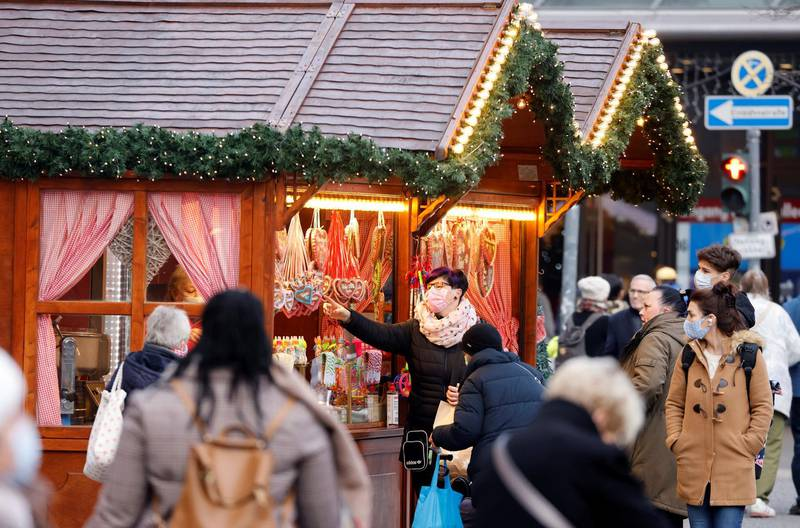 People wearing protective face masks walk beside Christmas-themed food stalls at Schloss Strasse shopping street, amid the coronavirus disease (COVID-19) outbreak in Berlin, Germany, December 1, 2020.    REUTERS/Fabrizio Bensch