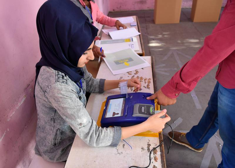 An Iraqi voter has his biometric voting card checked with his fingerprint upon arriving at a poll station in the northern multi-ethnic city of Kirkuk on May 12, 2018, as the country votes in the first parliamentary election since declaring victory over the Islamic State (IS) group. Polling stations opened at 7:00 am for the roughly 24.5 million registered voters to cast their ballots across the conflict-scarred nation. / AFP / Marwan IBRAHIM