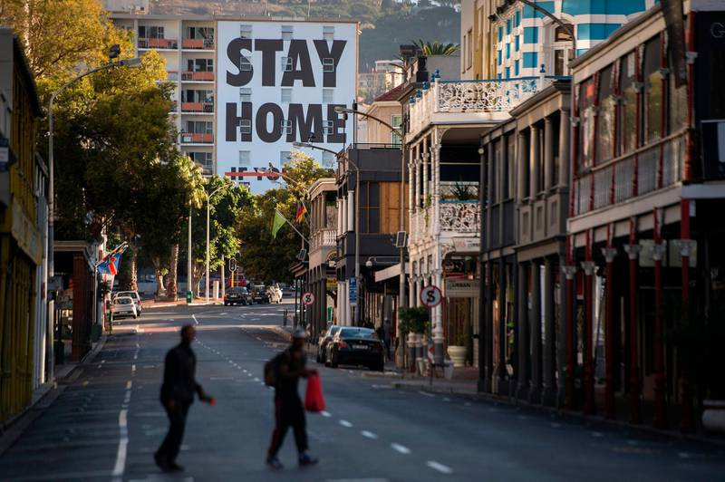 Two men walk across Long Street, usually one of the busiest and most popular entertainment areas with bars, clubs and restaurants in the city, with a billboard reading Stay Home, in Cape Town on April 3, 2020. South Africa came under a nationwide lockdown on March 27, 2020, joining other African countries imposing strict curfews and shutdowns in an attempt to halt the spread of the COVID-19 coronavirus across the continent. / AFP / RODGER BOSCH