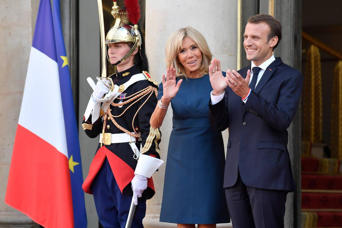 epa06893549 French President Emmanuel Macron and French First Lady Brigitte Macron wait for the France's national soccer team players at the Elysee Palace, in Paris, 16 July 2018. France won 4-2 the FIFA World Cup 2018 final against Croatia in Moscow, on 15 July.  EPA/JULIEN DE ROSA