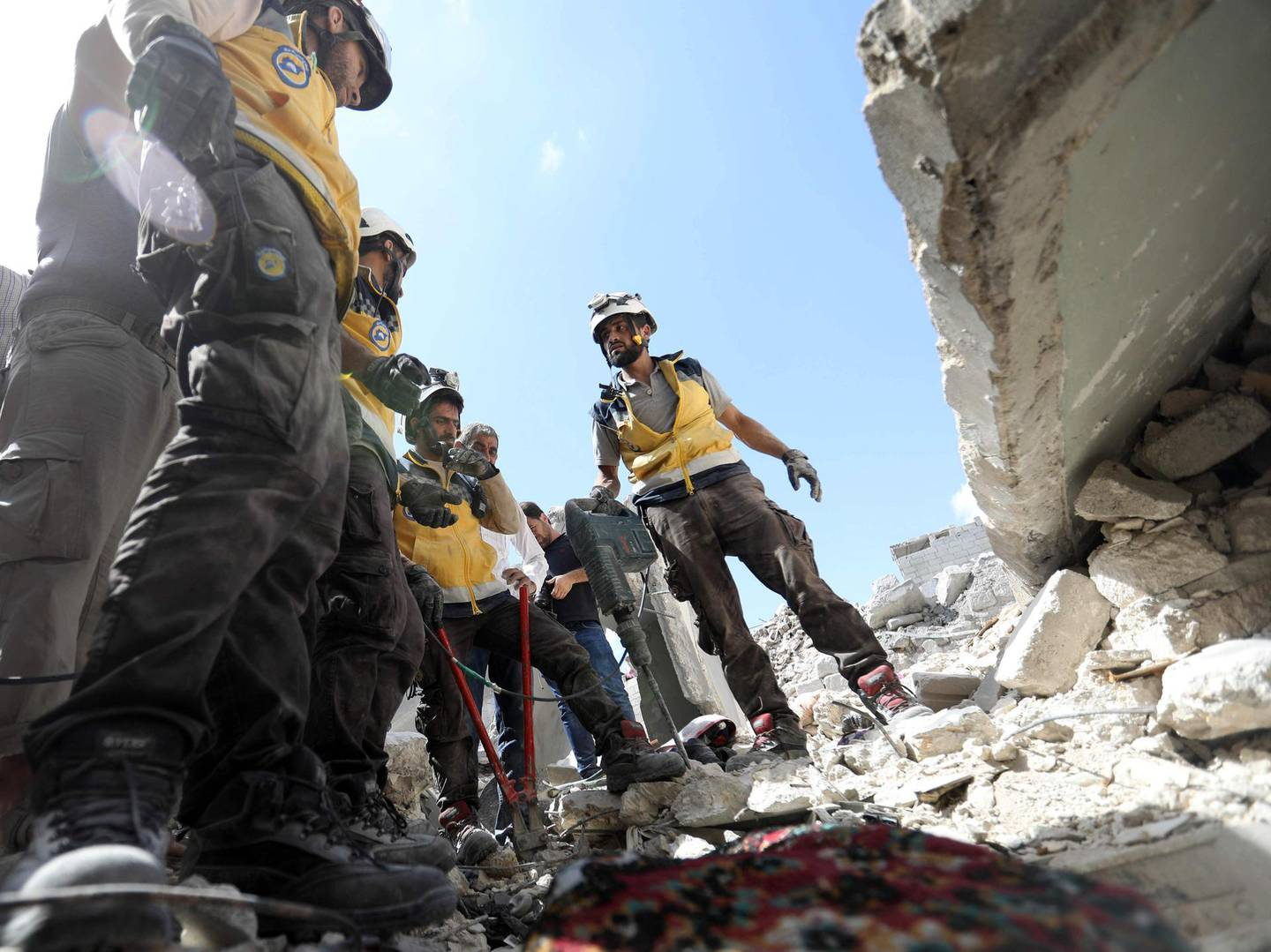 EDITORS NOTE: Graphic content / Members of the Syrian Civil Defence (White Helmets) uncover the body of a man killed in a collapsed building following a reported regime air strike on the town of Ariha, in the south of Syria's Idlib province, on July 12, 2019. At least a dozen civilians were killed in Syrian regime air strikes in the country's northwest, including three children, a war monitor said on July 12. / AFP / Omar HAJ KADOUR