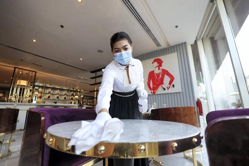 Dubai, United Arab Emirates - Reporter: N/A. News. Coronavirus/Covid-19. An employee at disinfects a table before welcoming customers in Dubai. Wednesday, November 11th, 2020. Dubai. Chris Whiteoak / The National