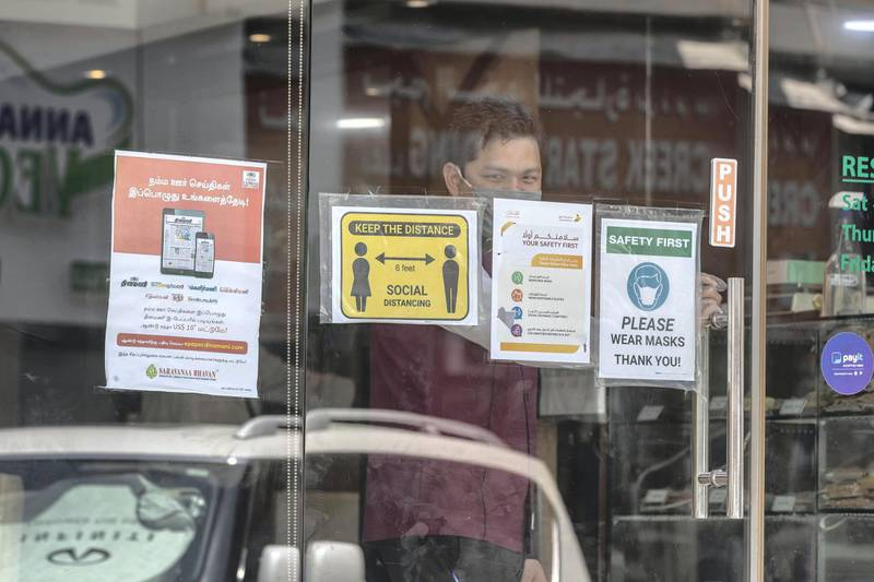 DUBAI, UNITED ARAB EMIRATES. 15 JUNE 2020. STANDALONE. Bur Dubai life during COVID-19.  A door man smile at the camera while waiting oinside a restaurant for patrons to arrive with COVID-19 warning outside. (Photo: Antonie Robertson/The National) Journalist: None. Section: National.