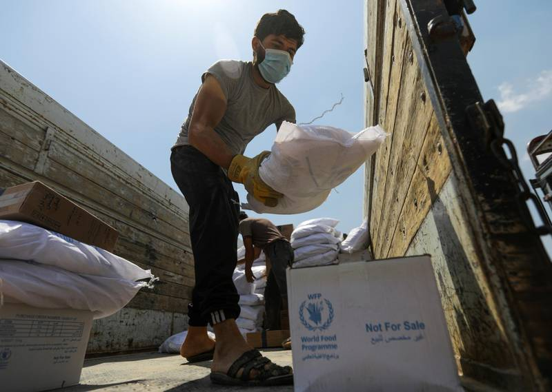 A worker unloads bags and boxes of humanitarian aid from the back of a truck in the opposition-held Idlib, Syria June 9, 2021. Picture taken June 9, 2021. REUTERS/Khalil Ashawi