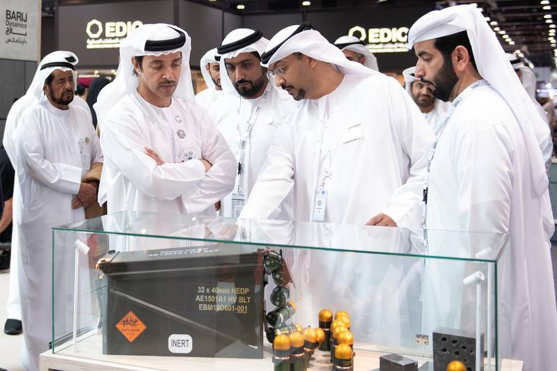 ABU DHABI, UNITED ARAB EMIRATES - February 17, 2019: HH Sheikh Hazza bin Zayed Al Nahyan, Vice Chairman of the Abu Dhabi Executive Council (L), inspects a weapon on the Barij Munition stand during a tour of the 2019 International Defence Exhibition and Conference (IDEX), at Abu Dhabi National Exhibition Centre (ADNEC).  ( Saeed Al Neyadi / Ministry of Presidential Affairs ) ---