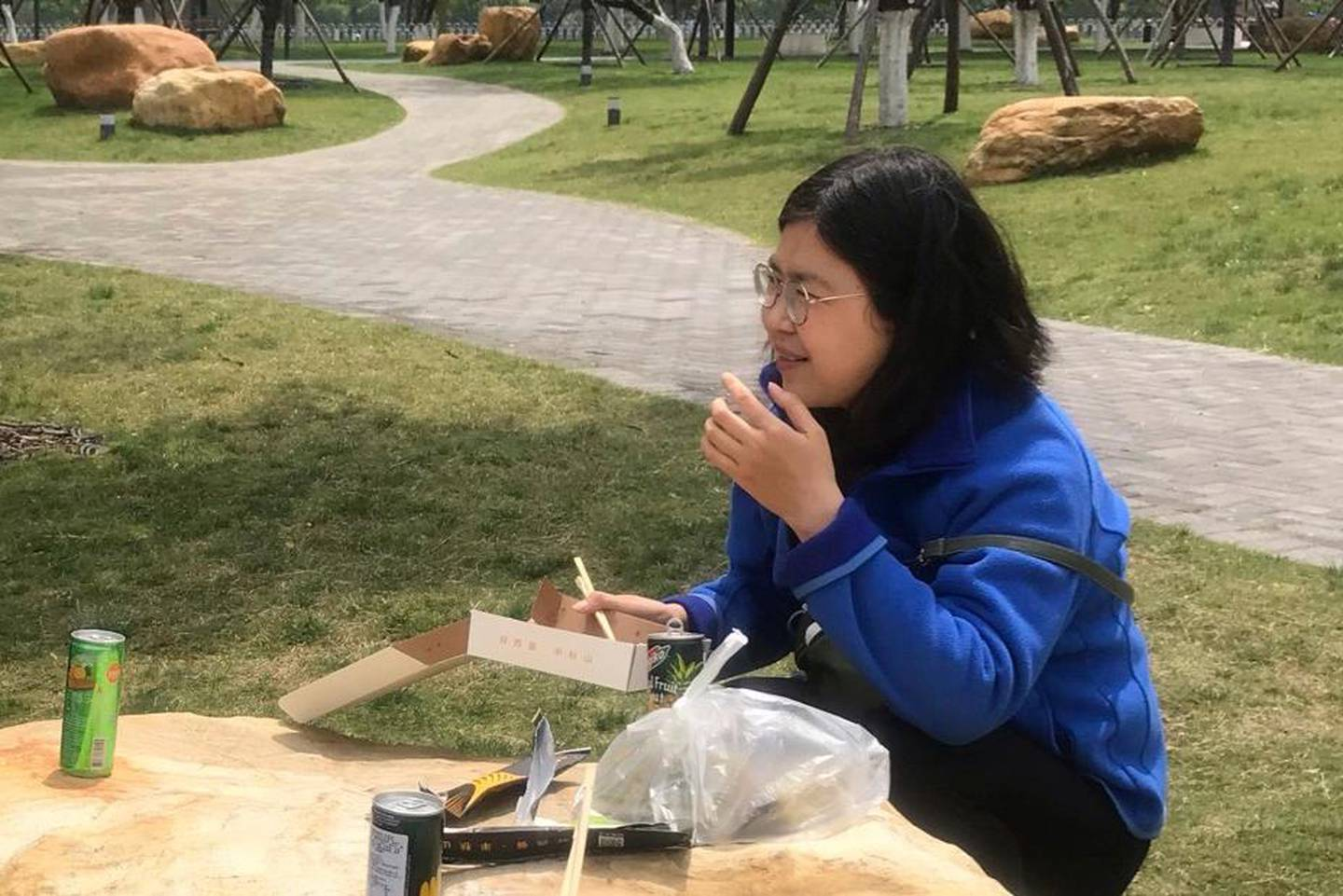"""In this photo taken April 14, 2020 and released by Melanie Wang, Zhang Zhan eats a meal at a park during a visit to Wuhan in central China's Hubei province. A Chinese court on Monday sentenced the former lawyer who reported on the early stage of the coronavirus outbreak to four years in prison on charges of """"picking fights and provoking trouble,"""" one of her lawyers said. (Melanie Wang via AP)"""