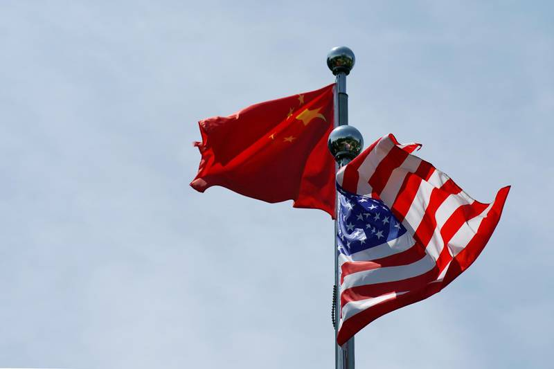 FILE PHOTO: Chinese and U.S. flags flutter near the Bund in Shanghai, China July 30, 2019.  REUTERS/Aly Song/File Photo