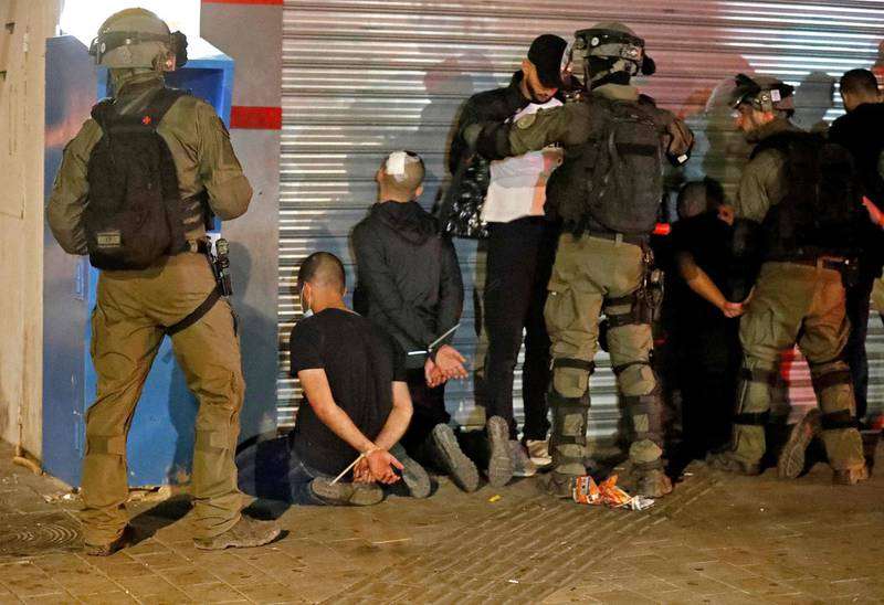Israeli forces detain a group of Arab-Israelis in the mixed Jewish-Arab city of Lod on May 13, 2021, during clashes between Israeli far-right extremists and Arab-Israelis. / AFP / Ahmad GHARABLI