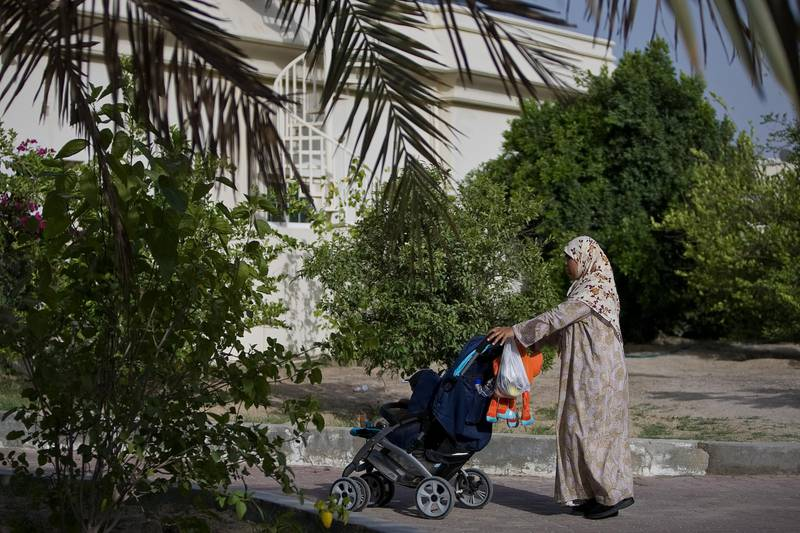 United Arab Emirates -Dubai- May 15, 2009:  HOUSE & HOME: A nanny takes a child out for a stroll in the Nad Al Sheba neighborhood in Dubai on Friday, May 15, 2009. Amy Leang/The National  *** Local Caption ***  amy_051509_nadalsheba_21.jpgamy_051509_nadalsheba_21.jpg