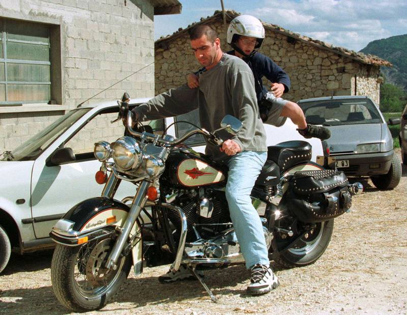 French soccer player Eric Cantona on his Harley Davidson motorcycle with his son on the back while on vacation in southern France May 21. Cantona announced his retirement from professional soccer on May 19. ReutersFRANCE CANTONA