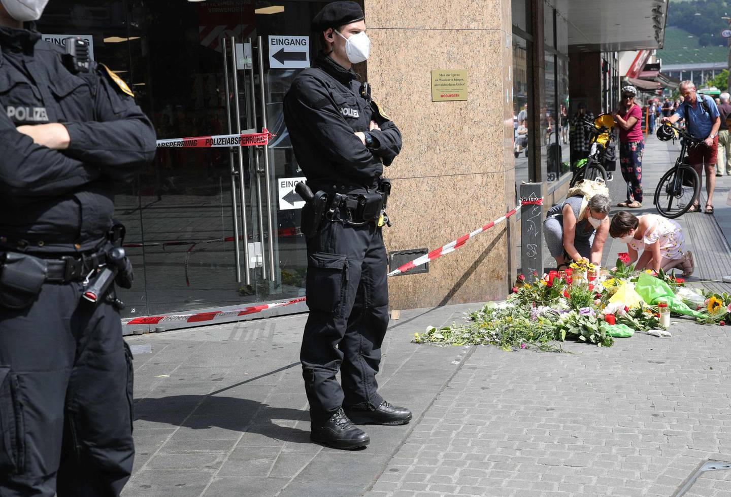 Policemen stand guard as people place flowers and candles at a makeshift memorial in tribute to the victims of a deadly attack in the city center of Wuerzburg, southern Germany, on June 26, 2021. Investigators were racing to pinpoint the motive of a man who went on a knife rampage in the German city of Wuerzburg, killing three people and leaving five seriously injured. The suspect, a 24-year-old Somali who arrived in Wuerzburg in 2015, staged the attack in the city centre on the evening of Friday, June 25, 2021, striking at a household goods store before advancing to a bank. / AFP / ARMANDO BABANI