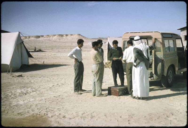 Jebel Dhana, Abu Dhabi 1963 Employees of one of the construction sites in Jebel Dhana buying bank drafts from the British Bank of the Middle East (BBME) mobile bank landrover to send money home to their families in India, Pakistan and many of the Middle East countries. The British Bank of the Middle East (BBME), Abu Dhabi town branch, offered a fortnightly banking service to all employees of various oil camps and construction sites based in and around Tarif & Jebel Dhana, as well as to Das Island, where offshore oil exploration was based. Photo by David Riley
