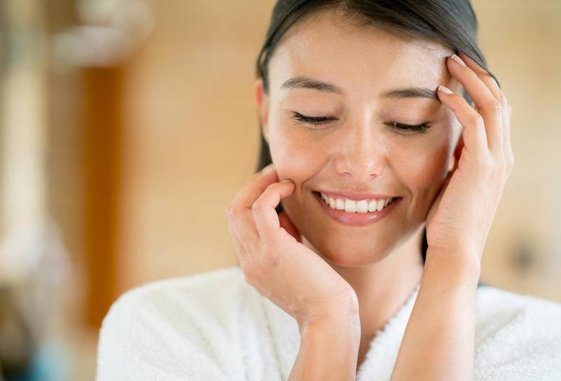 Beauty portrait of a woman in the bathroom touching her face and smiling - lifestyle concepts