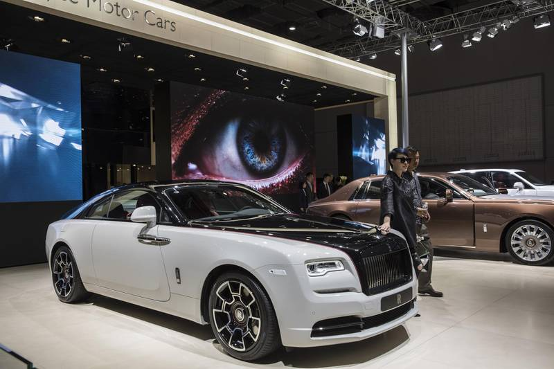 Attendees pose for photographs at the Rolls-Royce Motor Cars Ltd. stand at the Auto Shanghai 2019 show in Shanghai, China, on Thursday, April 18, 2019. China's annual auto show, held inShanghaithis year, opened to the media on April 16 amid the specter of an electric-carbubbleand as the world's largest auto market trudges through its first recession in a generation. Photographer: Qilai Shen/Bloomberg