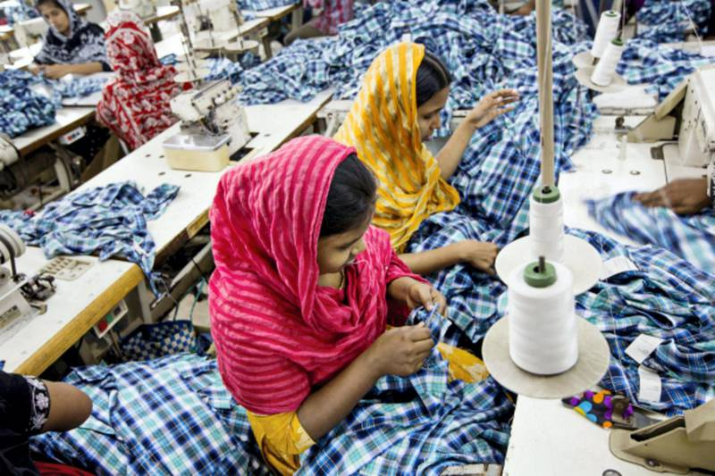 Workers sew plaid shirts on the production line of the Fashion Enterprise garment factory in Dhaka, Bangladesh, on Tuesday, April 30, 2013. Bangladesh authorities said they were accelerating rescue efforts at the factory complex that collapsed last week as hopes fade for more survivors after the nation's biggest industrial disaster. Bangladesh's labor law requires safety measures such as fire extinguishers and easily accessible exits at factories. Jeff Holt/Bloomberg